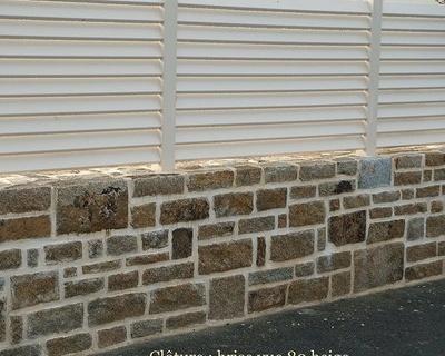 Clôture PVC beige sur mur en pierre