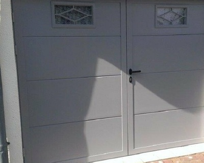 Porte de garage battante avec hublots décoratifs